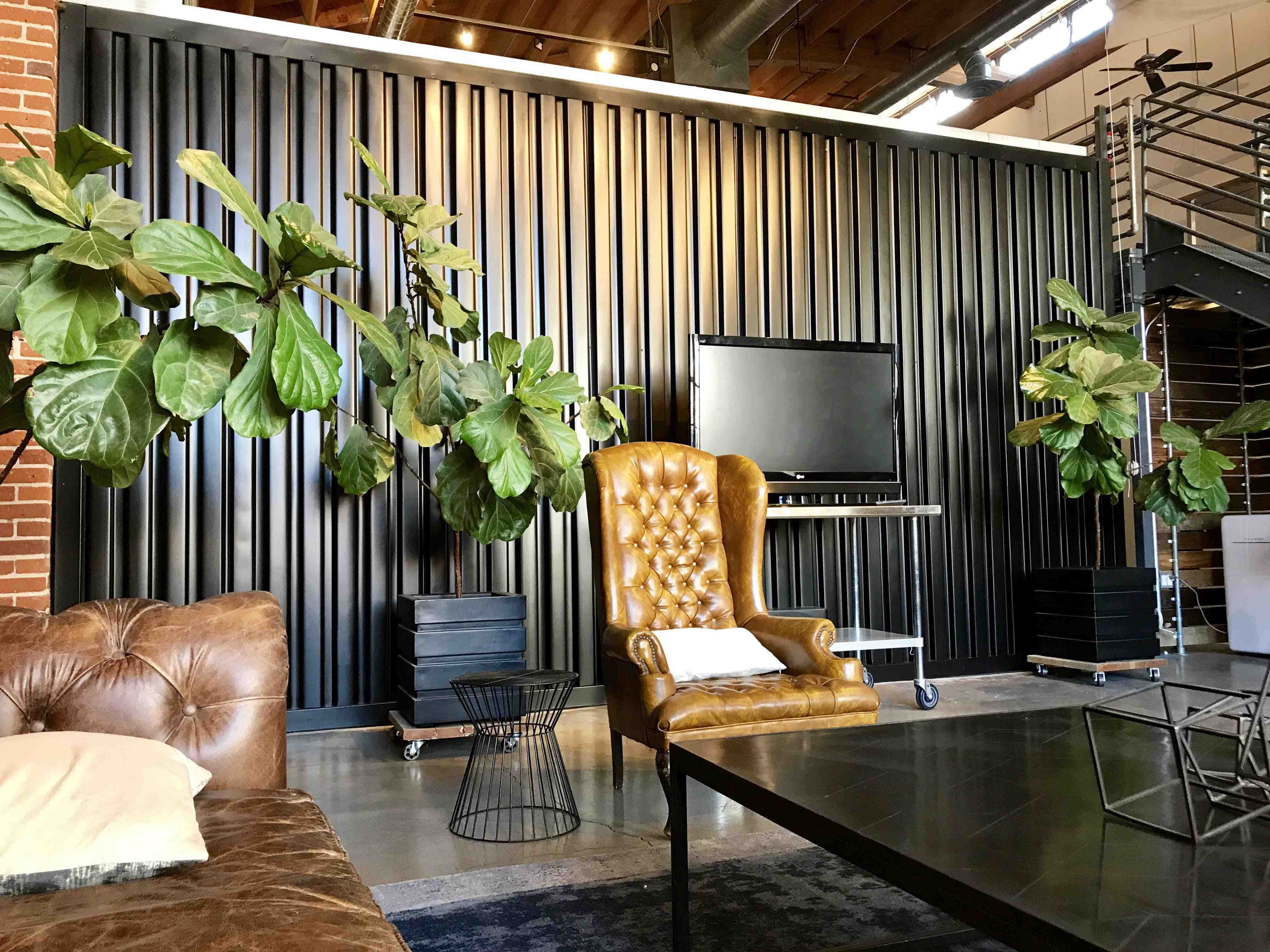 The waiting area of the Blink San Diego design studio has comfortable seating, fiddle leaf fig trees, and very high ceilings.
