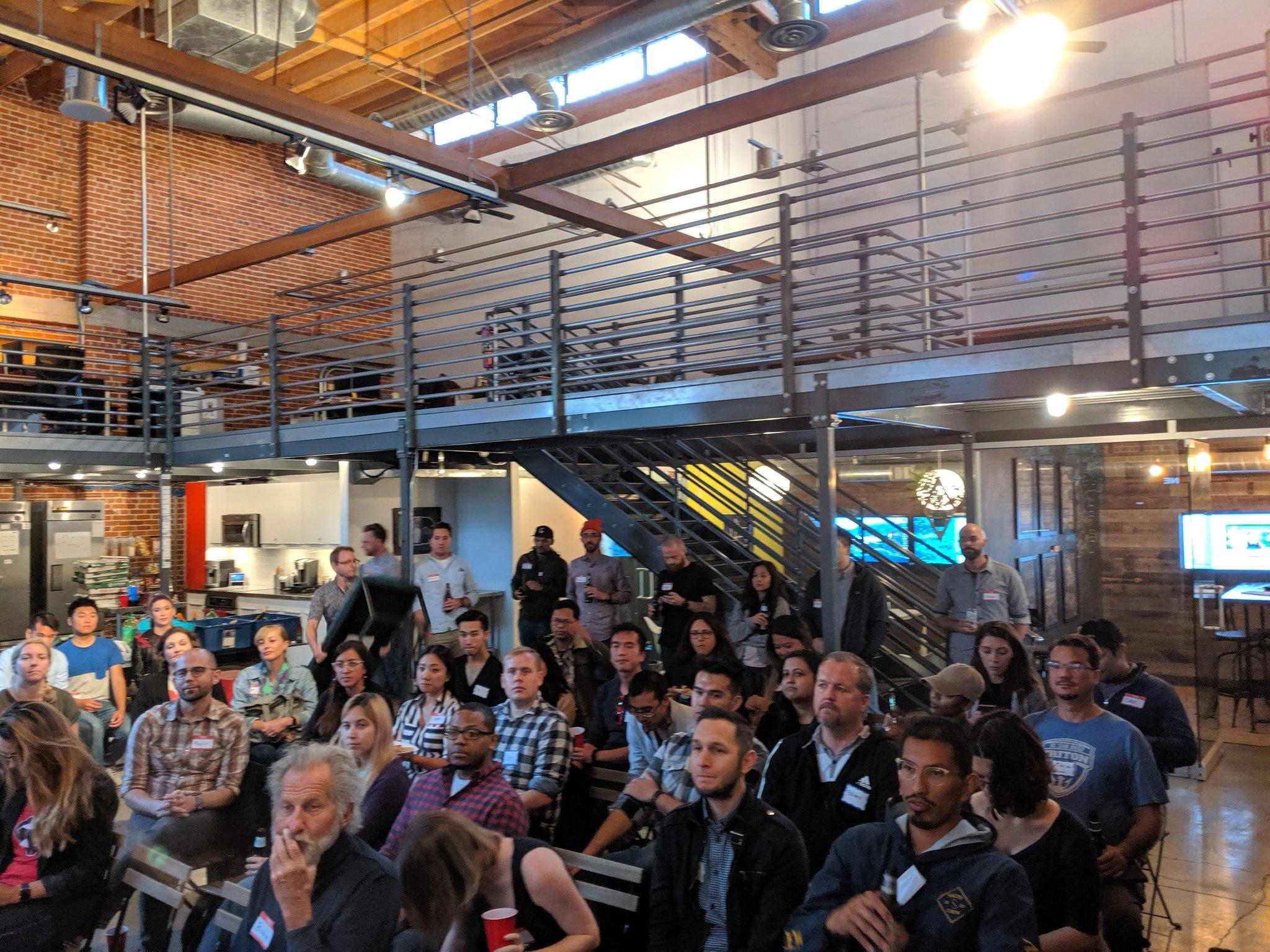 A crowd of designers, researchers, and engineers are seated in rows at Blink's San Diego studio for the event.