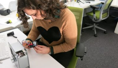 A photo of a person at a worktable examining a piece of computer hardware.