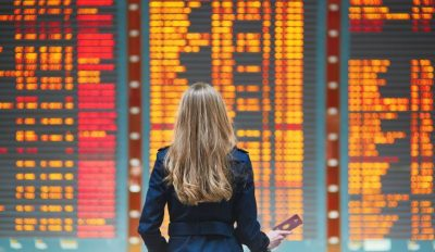 A photo of woman standing in front of an airport directory